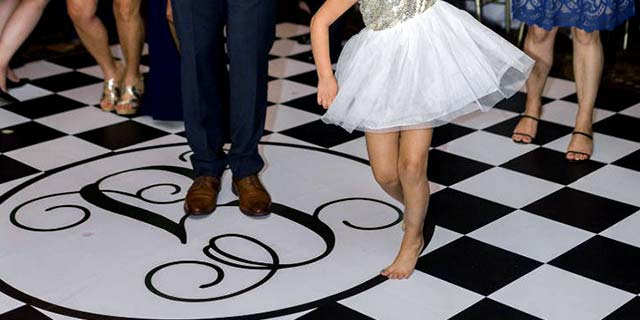 Checkered Vinyl Dance Floor with bride & groom dancing with guests